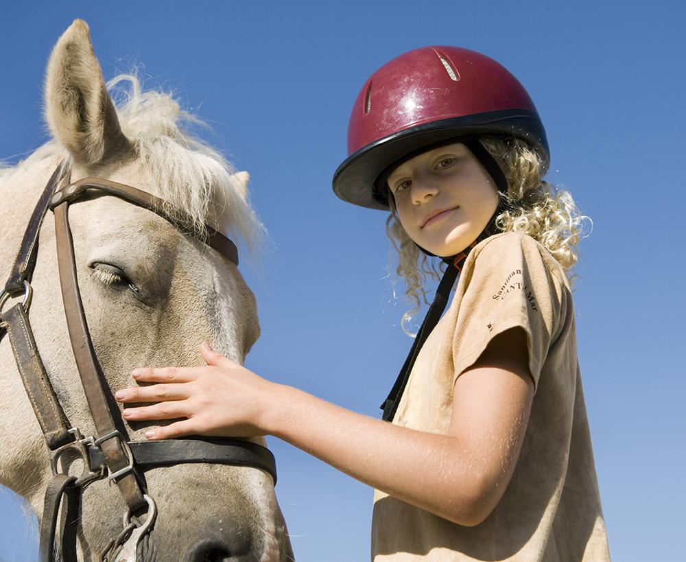 une jeune fille caresse un cheval